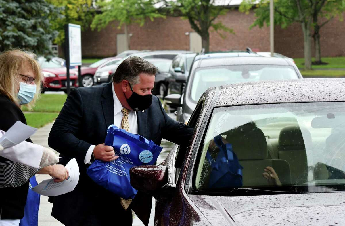 Albany County Executive Dan McCoy, center, and Albany County Department for Aging Commissioner Deb Riitano, left, distribute flu prevention bags to seniors in an effort to stem the spread of flu in Albany County on Wednesday morning, Sept. 2, 2020, at Congregation Beth Emeth in Albany, N.Y. The bags contained a thermometer, hand sanitizer, washable face mask, pill case, bottle of water and a can of chicken soup. (Will Waldron/Times Union)