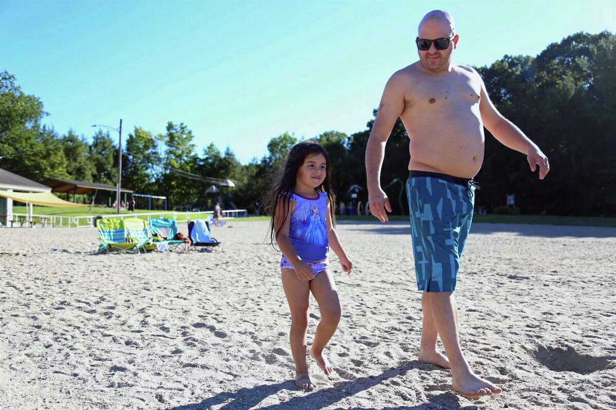 Ken Ruizzo of Fairfield and his daughter Talia, 3, head to the water at Lake Mohegan on Sunday, Aug. 30, 2020, in Fairfield, Conn.