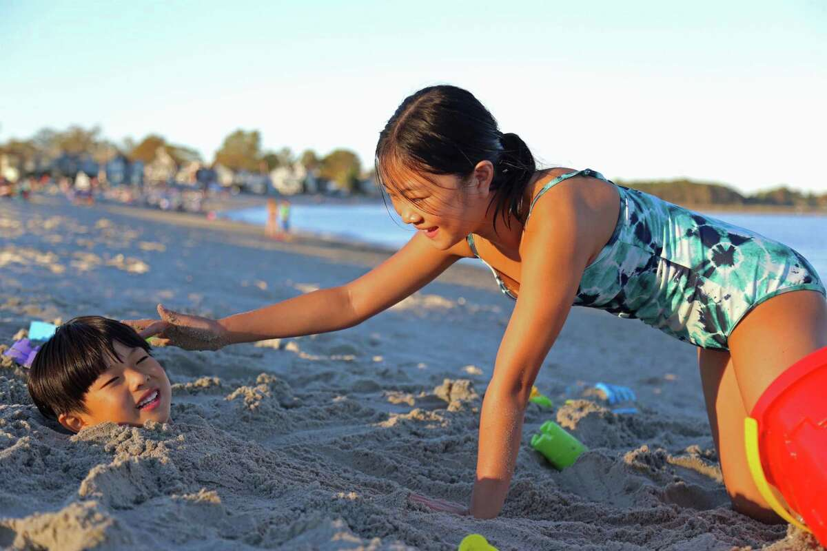 Makayla Tan, 10, of Westport, buries her brother, Tawin, 6, in the sand for a Sunday afternoon at Compo Beach on Aug. 30, 2020, in Westport, Conn.