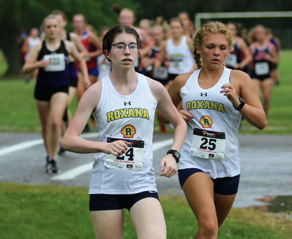 Roxana's Riley Doyle (left) and Zoey Losch run on the lead in the opening half-mile of the Carlinville Early Meet girls cross country race Tuesday at Loveless Park. Doyle and Losch finished 1-2 in the race.