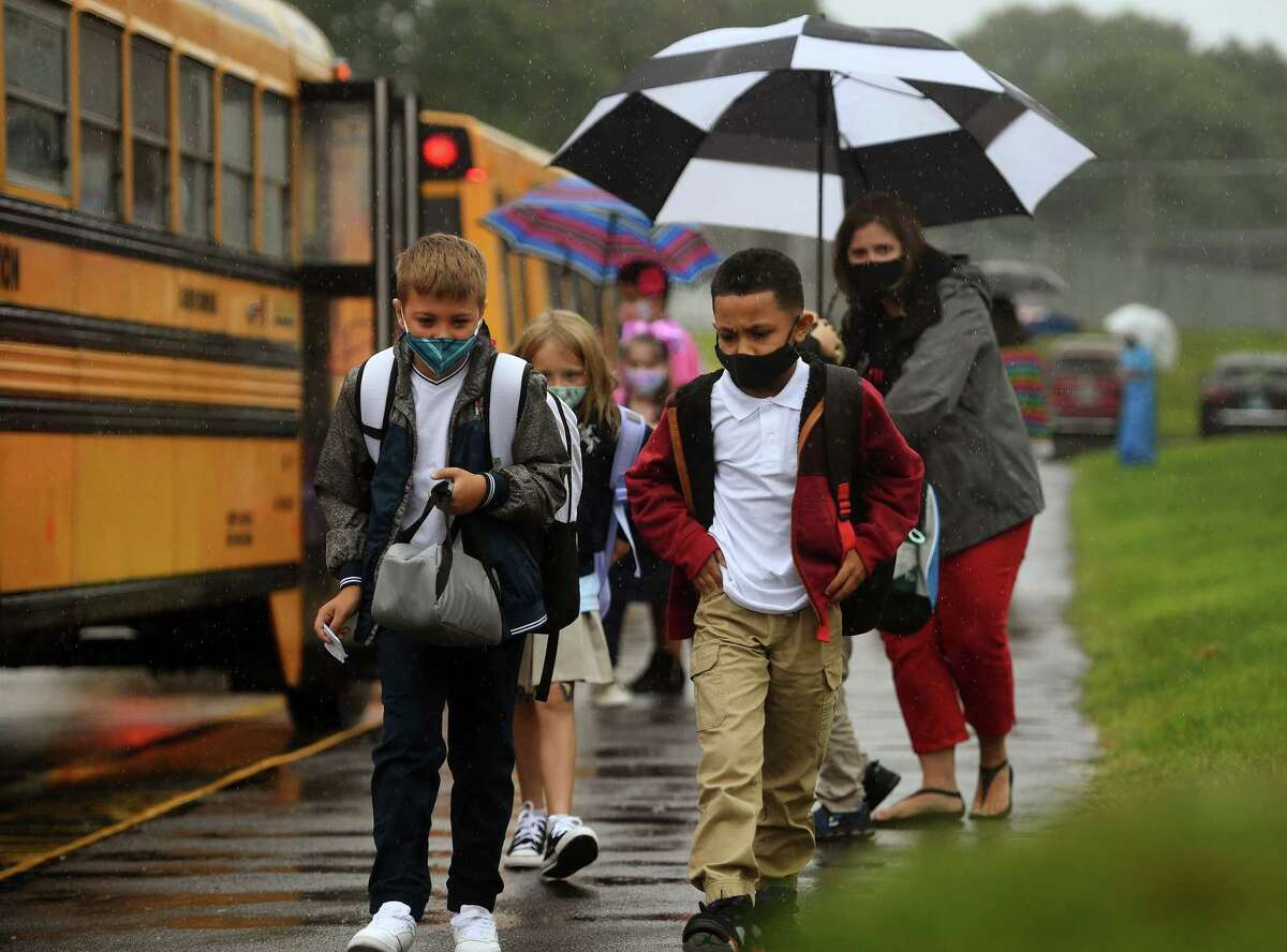 Students brave the rain as they exit the buses on the first day of school at Prendergast School in Ansonia, Conn. on Wednesday, September 2, 2020.