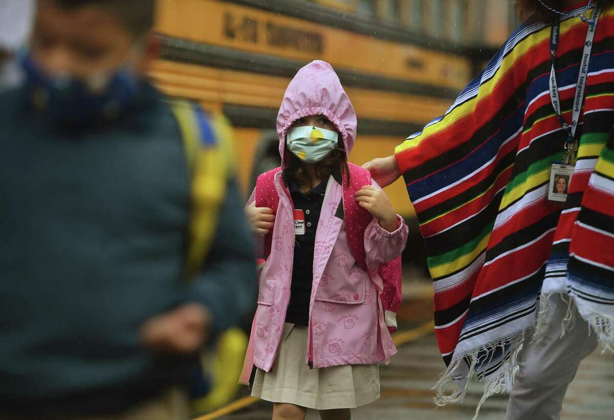 Students brave the rain as they exit the buses on the first day of school at Prendergast School in Ansonia, Conn. on Wednesday, September 2, 2020. In addition to the number of cases, other factors used to determine a region's risk level include whether COVID-19 hospitalizations are going down, increasing or remaining flat. The state's reopening standards are part of a