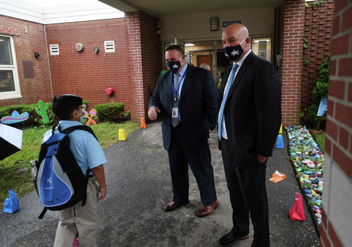 Ansonia Superintendent of Schools Joseph DiBacco, left, and Assistant Superintendent Stephen Bergin welcome students on the first day of school at Prendergast School in Ansonia, Conn. on Wednesday, September 2, 2020.