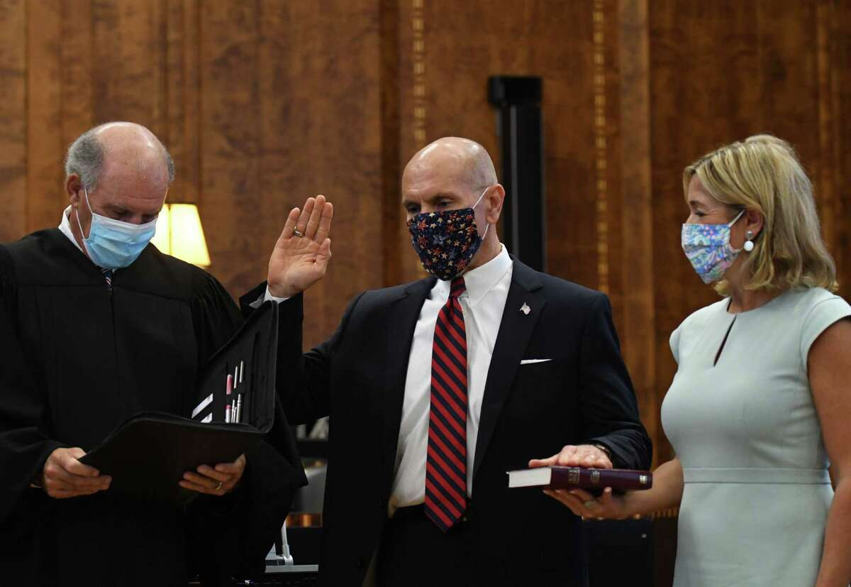 Judge Grant Jaquith, center, places his hand on a Bible held by wife, Rosemarie, as Chief Judge Glenn T. Suddaby, left, administers the oath of office for the former U.S. attorney's new role as a judge on the U.S. Court of Appeals for Veteran Claims on Wednesday, Sept. 2, 2020, at James T. Foley Federal Courthouse in Albany, N.Y. Judge Jaquith is the former U.S. attorney for New York's Northern District. He is succeeded by Antoinette Bacon. (Will Waldron/Times Union)