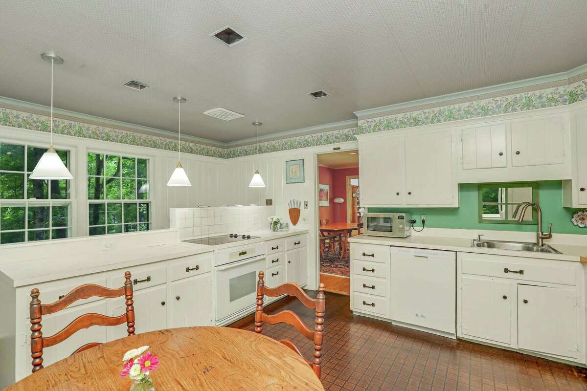 In the sunny eat-in kitchen features include ample counter spaces, cabinetry, and a door to the patio.