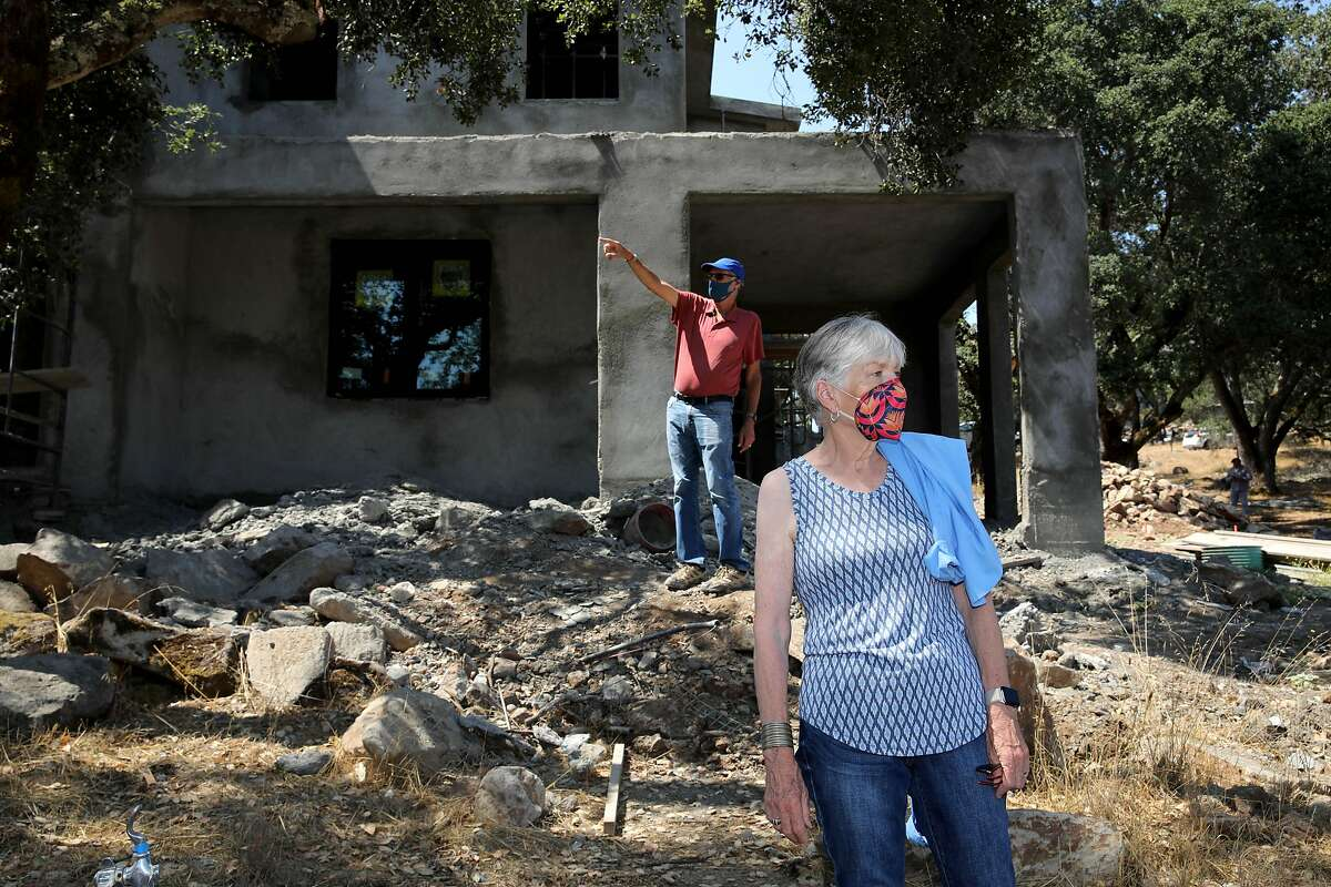 Frank Tansey and his wife Nancy Watson-Tansey stand in the back of their home at 2877 Rollo Rd. on Thursday, August 27, 2020, in Santa Rosa, Calif. Their original home was destroyed in a wildfire. Sara Harrison Woodfield is the architect of the home under construction.