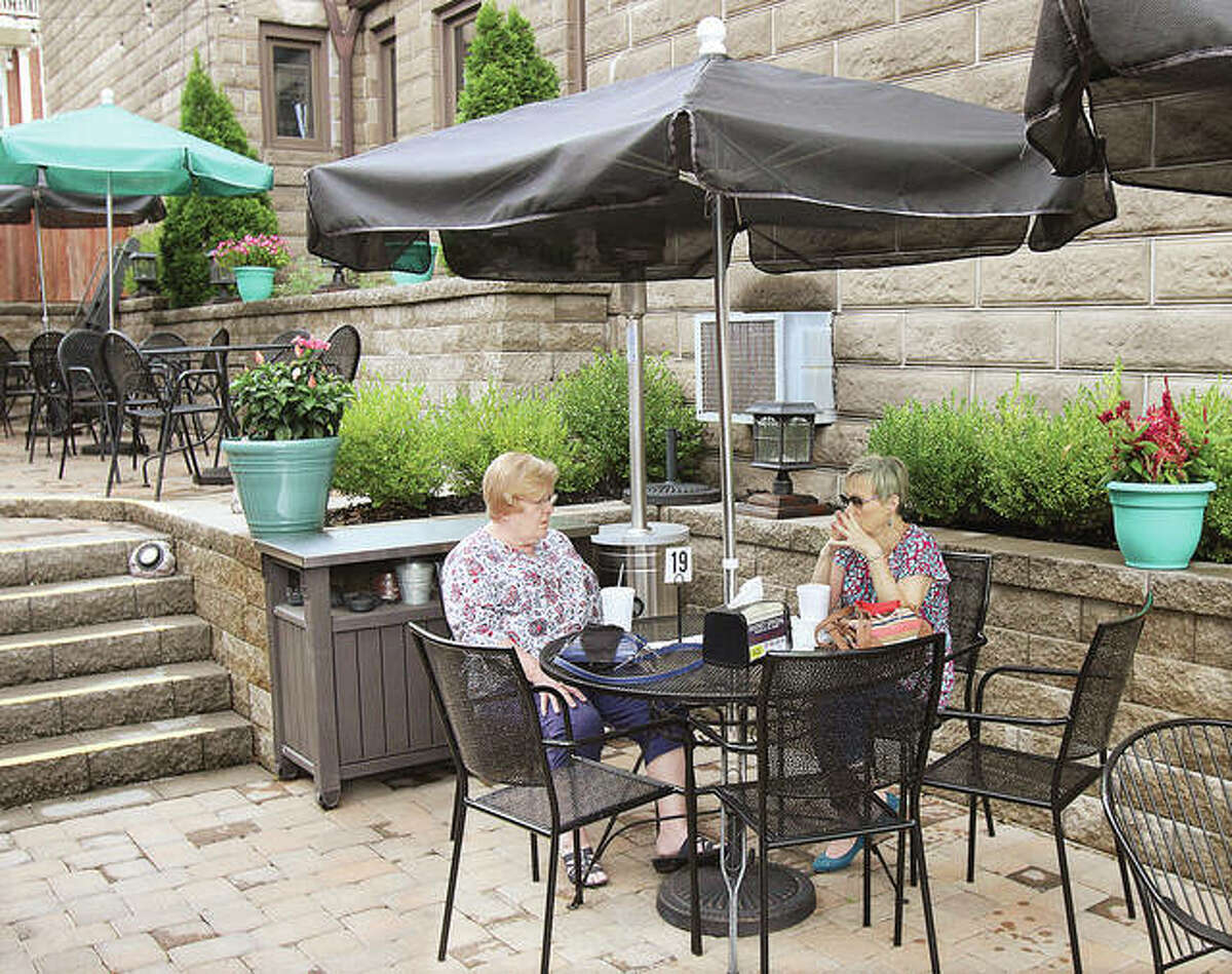 Two women wait for their lunch Wednesday in the outdoor dining space between the Brown Bag Bistro and the 1904 General Store on East Broadway in Alton. New rules restricting restaurants and bars to outdoor service only in the Metro East went into effect Wednesday.