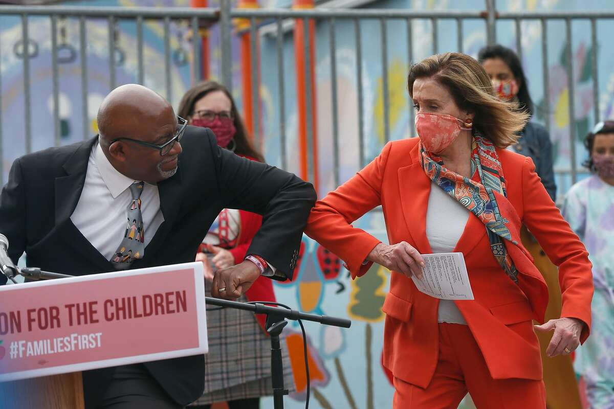 House Speaker Nancy Pelosi bumps elbows with S.F. schools Superintendent Vincent Matthews after he introduced her during a news conference.