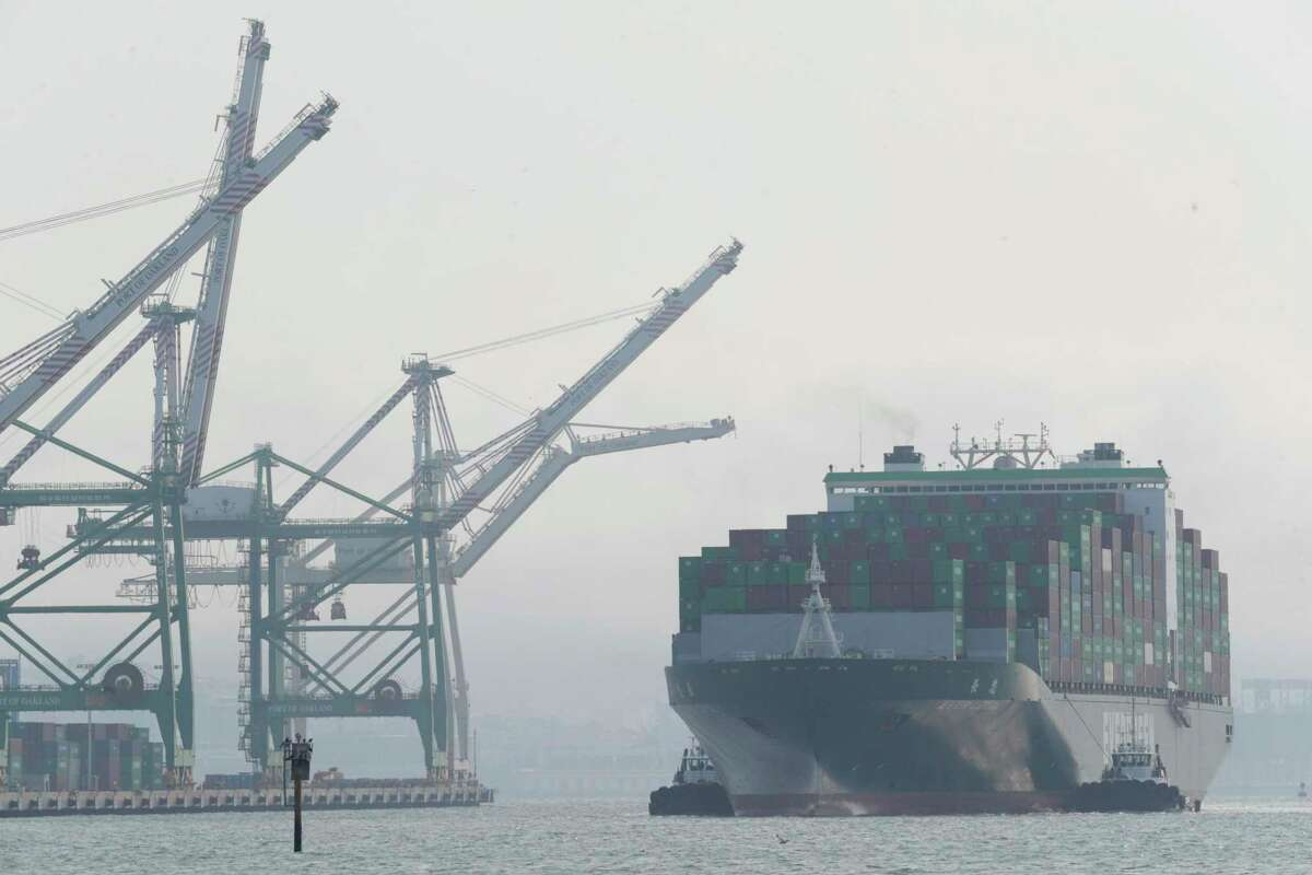 Tug boats guide a container ship in to the Port of Oakland as a mixture of smoke and fog reduces visibility in the bay.