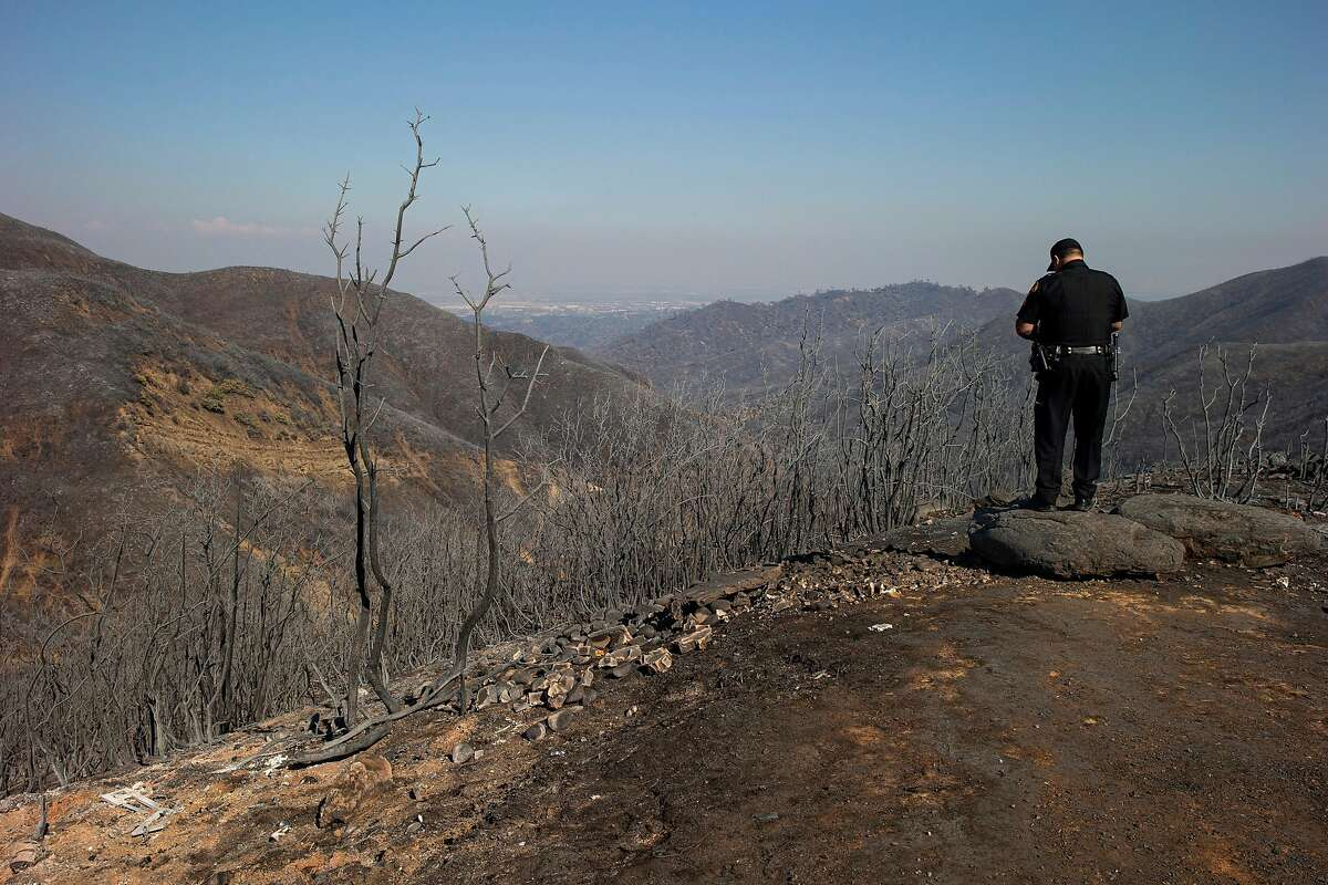 After a fire destroyed the area along Blue Ridge Road, a sheriff's deputy views the aftermath on Thursday, Aug. 27, 2020, in Vacaville, Calif. The LNU Lightning Complex fires are 35% contained and have been active for 10 days, according to CalFire's latest report Thursday. The fires have burned more than 370,000 acres.