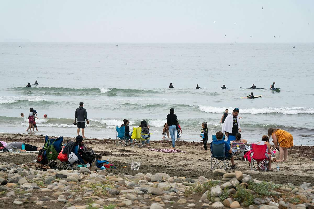 People gather at Pacifica State Beach on a gloomy summer day in Pacifica, Calif., on Sunday, August 16, 2020.