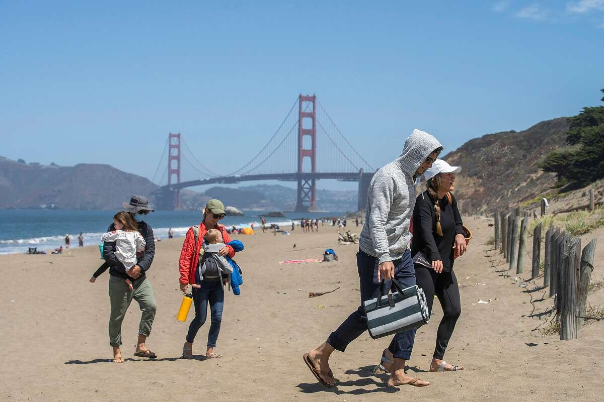 A group of people leave Baker Beach on Thursday, Aug. 13, 2020, in San Francisco, Calif.