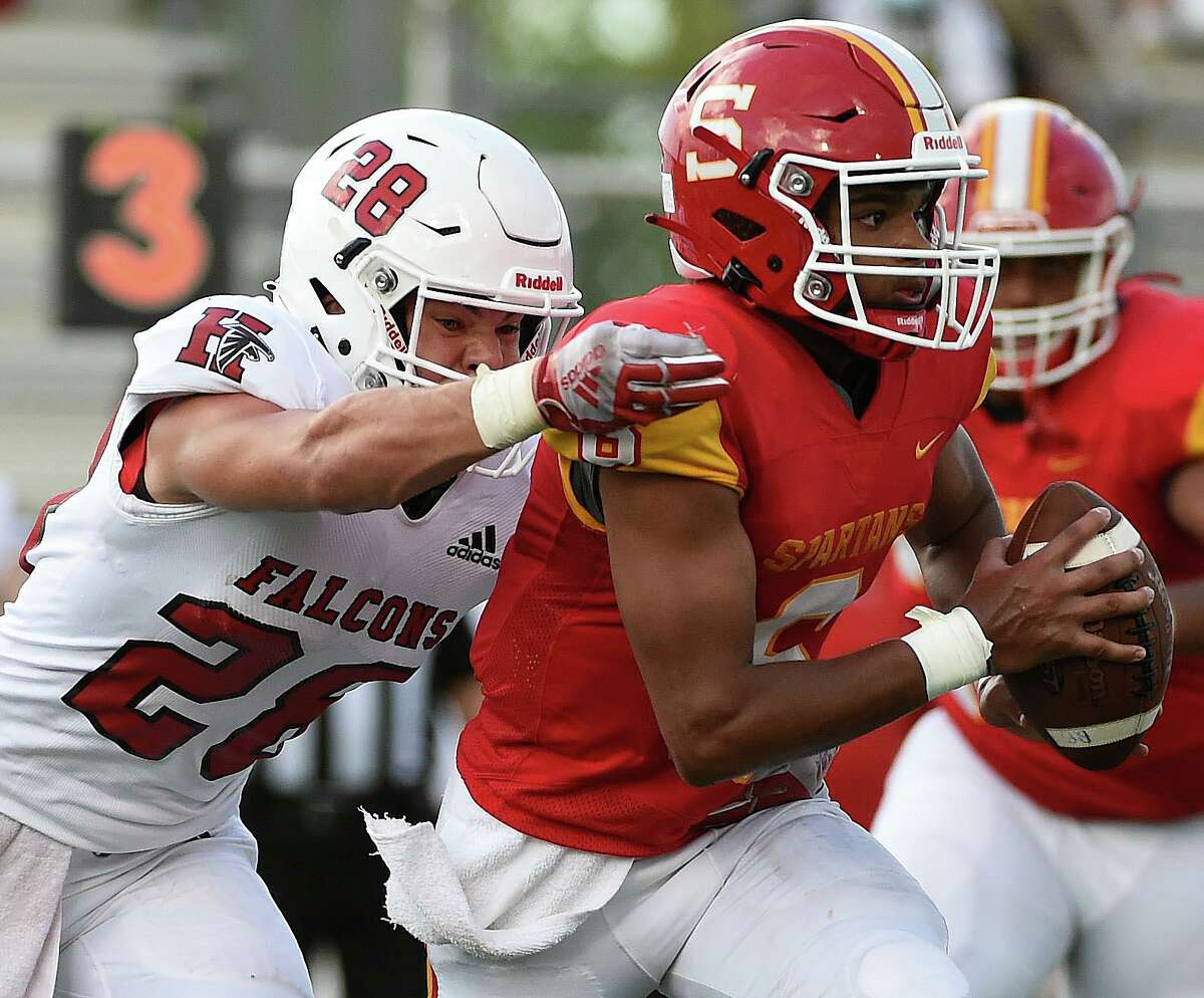 Stafford quarterback Brayden Baptiste, right, tries to escape the tackle of Huffman linebacker Wyatt Kasper during the first half of a high school football game on Saturday,in Stafford.