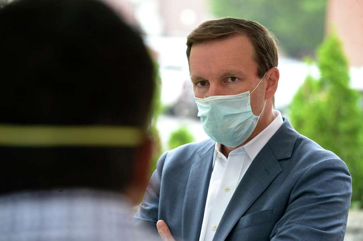 U.S. Sen. Chris Murphy listens to Shinu Simon, Administrative Director of the community health center Connecticut Institute for Communities, during a visit to the facility to promote increased COVID-19 testing. Friday, July 17, 2020, in Danbury, Conn.