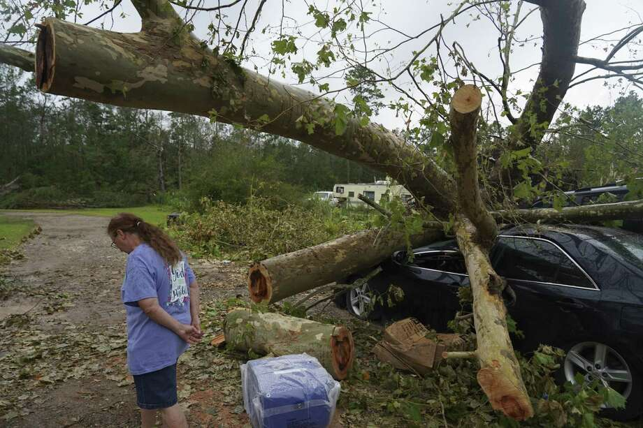 A person stands in front of a vehicle damaged by a fallen tree after Hurricane Laura made landfall near Orange, Texas, U.S., on Friday, Aug. 28, 2020. Hurricane Laura, one of the most powerful storms ever to hit Louisiana, left a path of chemical fires, wrecked buildings, flooded roads and what could be more than $15 billion in insured losses, with reports of at least six people dead. Photographer: Go Nakamura/Bloomberg Photo: Go Nakamura / Bloomberg / © 2020 Bloomberg Finance LP