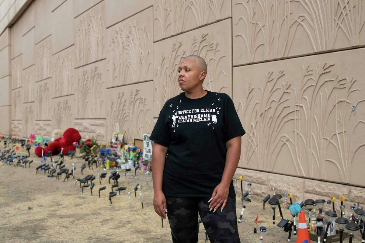 Candice Bailey poses at the Elijah McClain memorial in Aurora, Colo., on Aug. 19, 2020.