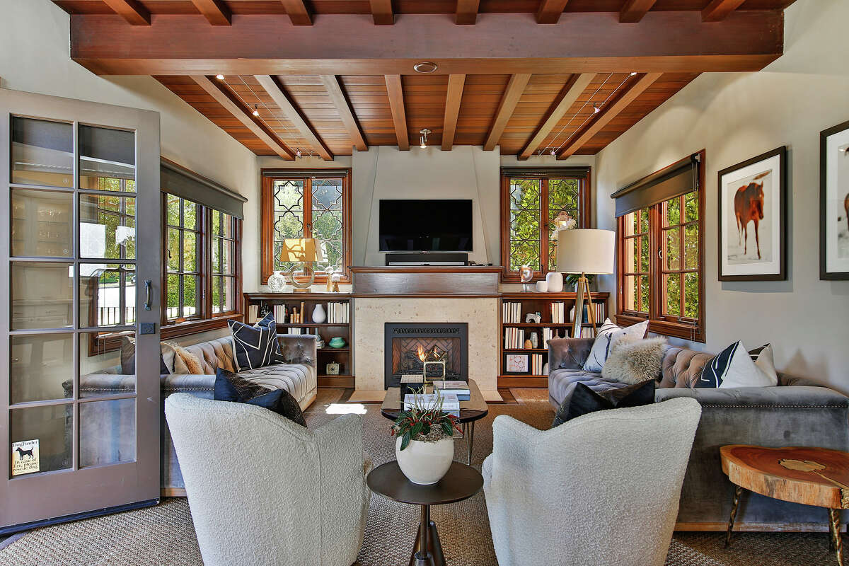 The drama of exposed beams and dark wood is softened by ample natural light and multiple fireplaces.