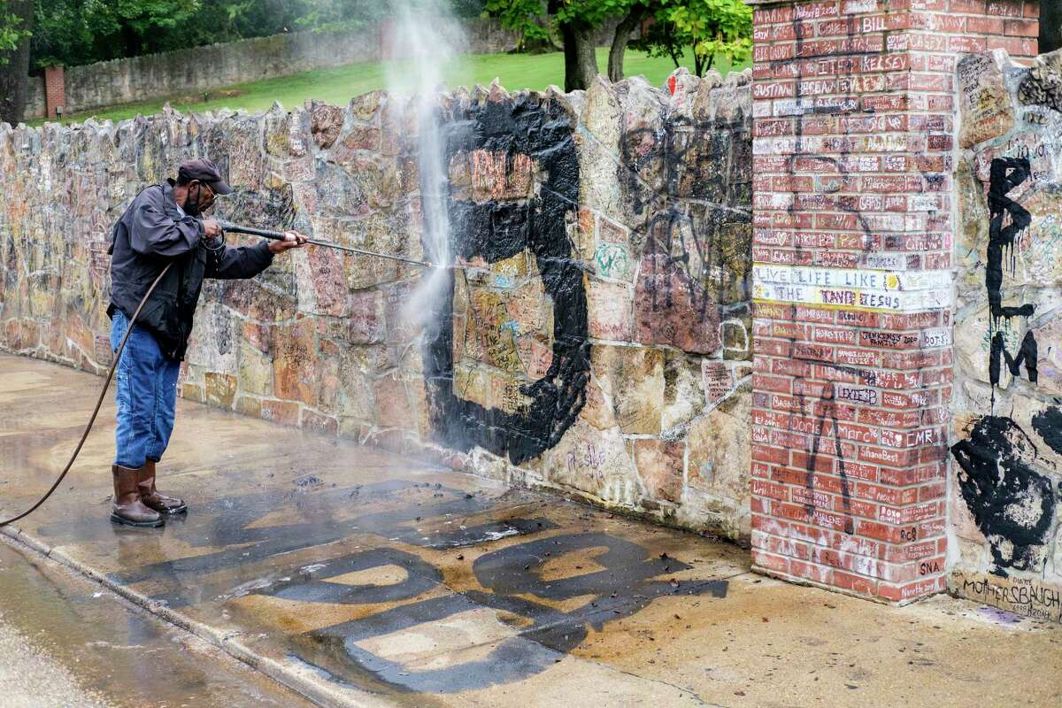 EDS NOTE: OBSCENITY - A worker power washes spray paint off the walls and sidewalk outside Graceland on Tuesday, Sept. 1, 2020, in Memphis, Tenn. Graffiti phrases were found on several tourist attractions in Tennessee on Monday night, including Graceland, the Levitt Shell Amphitheater in Overton Park and the a€œI Heart Memphisa€ mural in midtown Memphis. (Brandon Dahlberg/The Commercial Appeal via AP)