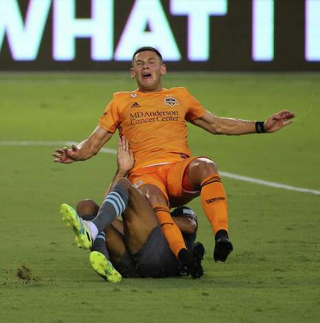 Houston Dynamo forward Christian Ramirez (13) falls onto Minnesota United defender James Musa (41) while battling during the first half of a MLS match Wednesday, Sept. 2, 2020, at BBVA Stadium in Houston. Photo: Yi-Chin Lee, Staff Photographer / © 2020 Houston Chronicle