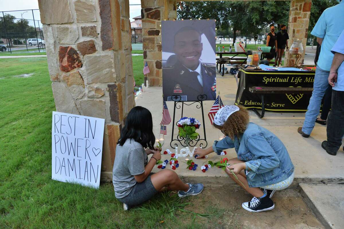 Kassidy Alvarez and Cheyenne Smith light candles during a memorial vigil Wednesday evening for Damian Daniels who was killed by Bexar County Deputies during a struggle over a handgun last week.