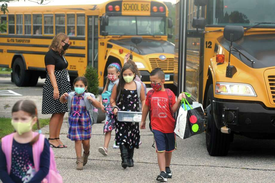 Principal Kelly Svendsen greets students as they arrive for the first day of classes at Monroe Elementary School, in Monroe, Conn. Sept. 1, 2020. Photo: Ned Gerard / Hearst Connecticut Media / Connecticut Post