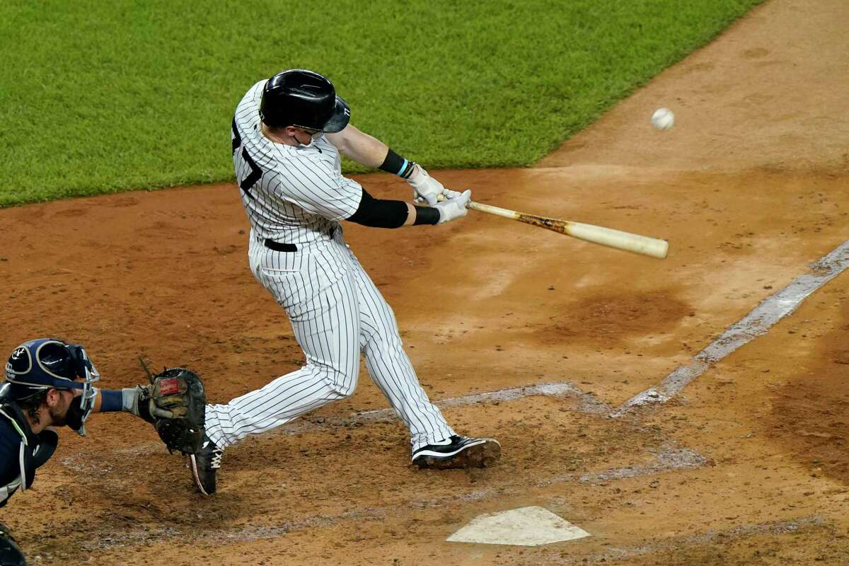 New York Yankees designated hitter Clint Frazier hits a solo home run during the sixth inning of a baseball game against the Tampa Bay Rays, Wednesday, Sept. 2, 2020, at Yankee Stadium in New York. Rays catcher Kevan Smith is behind the plate. (AP Photo/Kathy Willens)