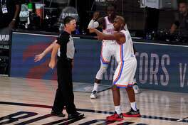 Referee Pat Fraher (26) listens as Oklahoma City Thunder's Chris Paul, right, and Dennis Schroder, rear, make their case after a foul call was made against the Houston Rockets late in the second half of an NBA first-round playoff basketball game in Lake Buena Vista, Fla., Wednesday, Sept. 2, 2020. (AP Photo/Mark J. Terrill)
