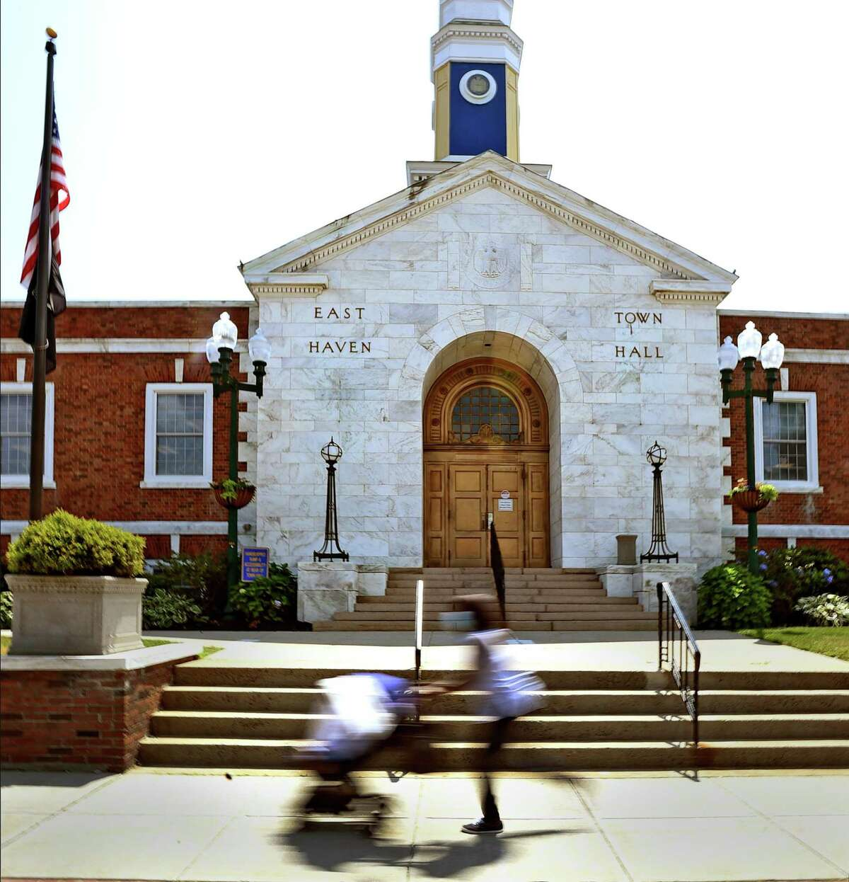 A woman pushes a baby stroller past East Haven Town Hall.