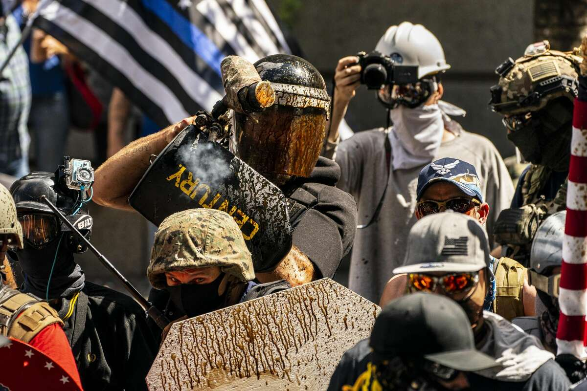Alan Swinney, a far-right demonstrator, fires paintballs while clashing with counter-protesters outside of the Multnomah County Justice Center in Portland, Ore., Aug. 22, 2020. Right-wing and left-wing groups clashed here for hours on Saturday, while police watched from a distance without intervening. (David Ryder/The New York Times)