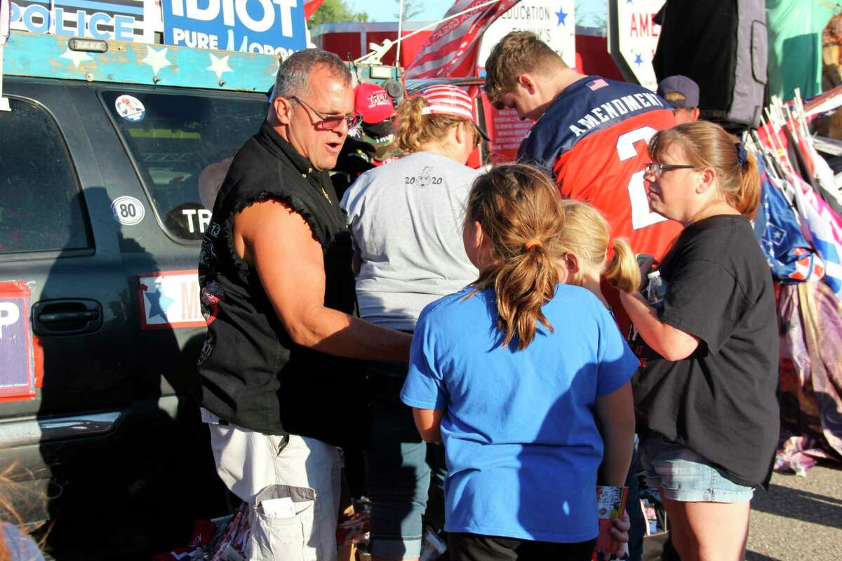 Rob Cortis, left, sells merchandise as his Trump Unity Bridge appeared in Bad Axe on Wednesday evening. He has been touring the country with his creation since 2016. See more photos from the event on Page 8A. (Robert Creenan/Huron Daily Tribune)