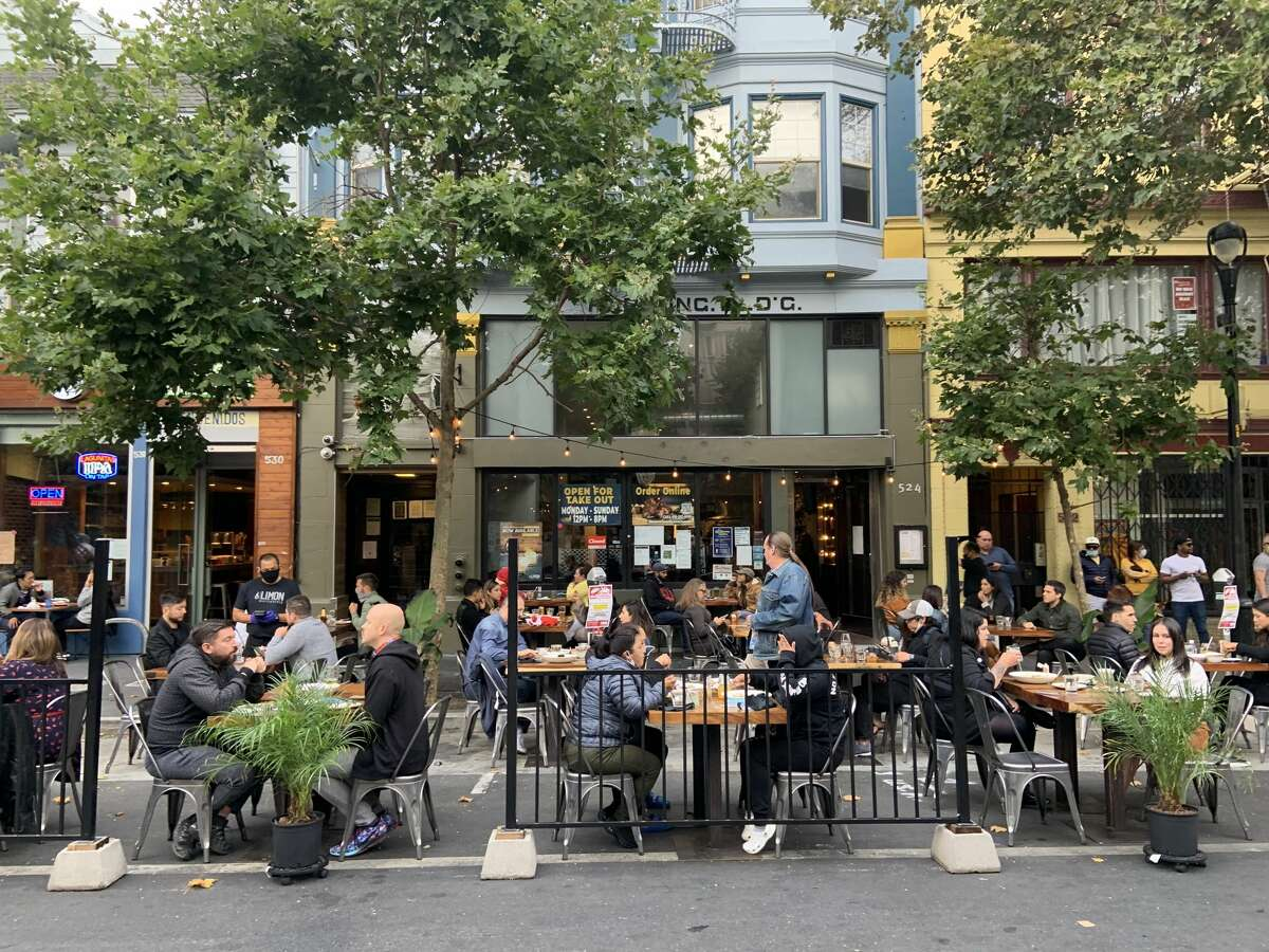 People dine out amid the coronavirus pandemic on San Francisco's Valencia Street in August 2020.