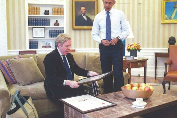 President Barack Obama presents a birthday gift to designer Michael S. Smith in the Oval Office in an undated photo. Smith gave a new look to the Oval Office, with hand-printed striped wallpaper that set off the room's architectural details and modern pieces mixed in with the antiques.