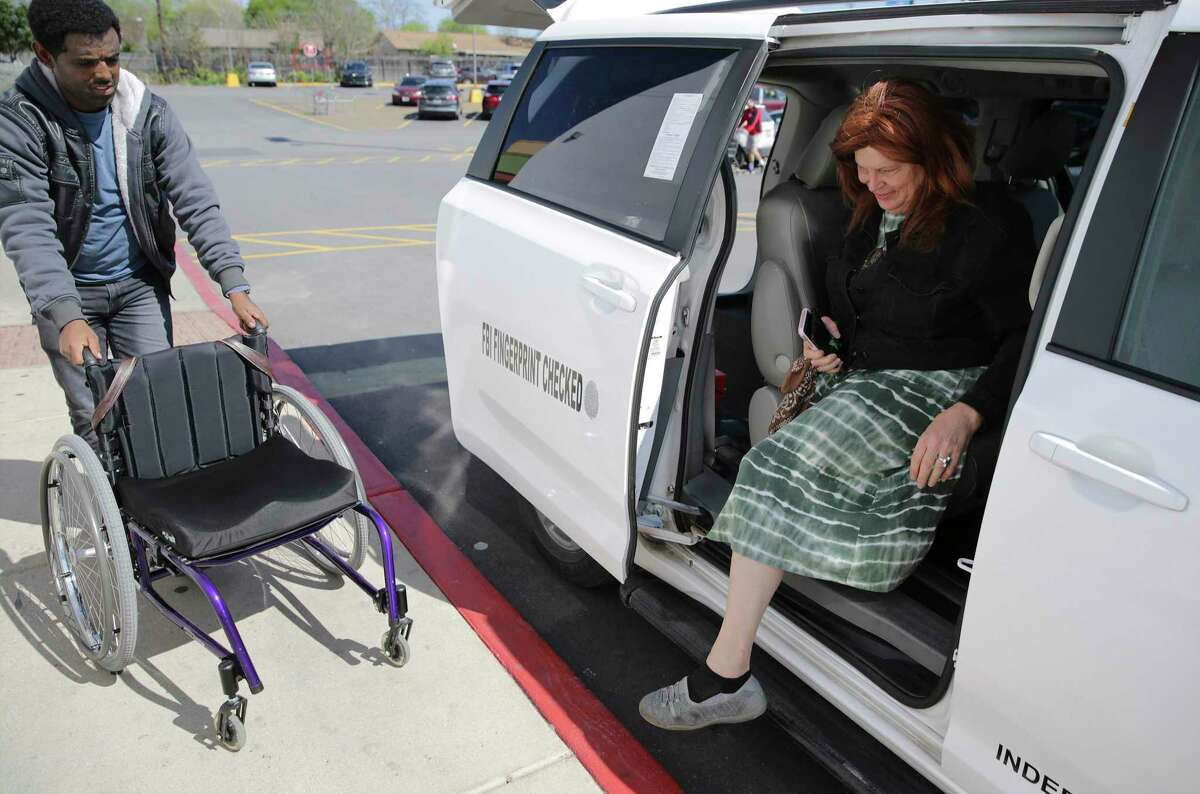 A VIA LINK driver brings Christa Williams' wheelchair to her as she gets dropped off at an H-E-B on Feb. 21, 2020 in San Antonio. Williams said she uses the service one to two times a week. VIA allows riders to request trips via smartphone app, something Metropolitan Transit Authority will test starting Sept. 8.