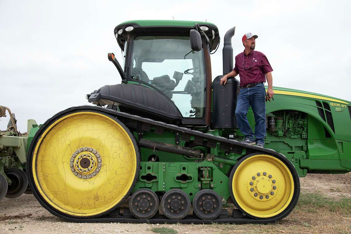 Boening stands on a tractor in a field where he grew grain sorghum, which already has been harvested.