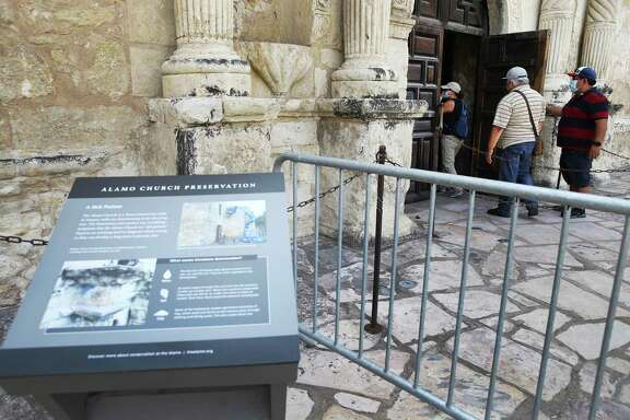 Visitors open the door to enter as the Alamo re-opens its iconic mission-era church to the public on Thursday, Sept. 3, 2020. After the state's most recognized building had been closed for nearly six months due to COVID-19, guests can tour the interior of the church once again. The mission and battle site now requires visitors to order free tickets on its website, thealamo.org. Occupancy is limited to 50 people for 30 minutes intervals inside the church during a self-guided tour. Face coverings and social distancing are still required.