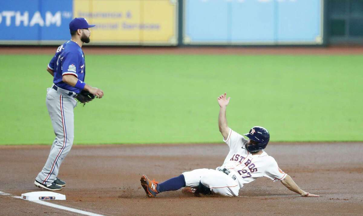 Houston Astros Jose Altuve (27) slide into third base as Yuli Gurriel lined out sharply Texas Rangers right fielder Joey Gallo during the first inning of an MLB baseball game at Minute Maid Park, Thursday, September 3, 2020, in Houston.