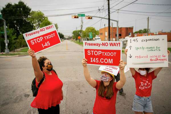 Desiree Alejandro, left, and Danielle Sullivan, center, hold up signs in the middle of the street during a demonstration at the intersection of Polk and St. Emanuel east of downtown Houston on Sept. 3, 2020. The Texas Department of Transportation's plans to rebuild Interstate 45 between downtown and Greenspoint would close Polk Street along with negatively impacting communities north of downtown, critics say.