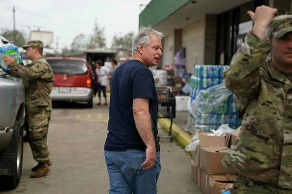 Mayor Mike Danahay, center, visits Care Help, where Army National Guard soldiers, and volunteers distributed goods to people in need Tuesday, Sept. 1, 2020, in Sulphur, La. The city of more than 20,000 people was heavily affected by Hurricane Laura.