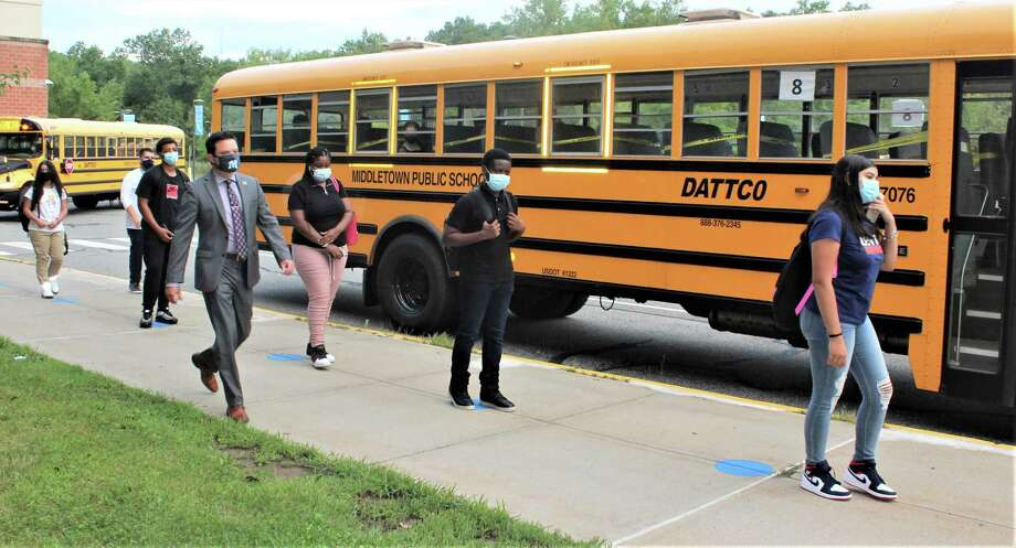 Middletown Public Schools began the 2020-21 academic year Thursday. Here, high school students get off their buses, ready to queue up on blue dots placed six feet apart. All must enter the buildings in this way, where they will be thermal scanned for temperatures to avoid possibly spreading the coronavirus. Photo: Cassandra Day / Hearst Connecticut Media