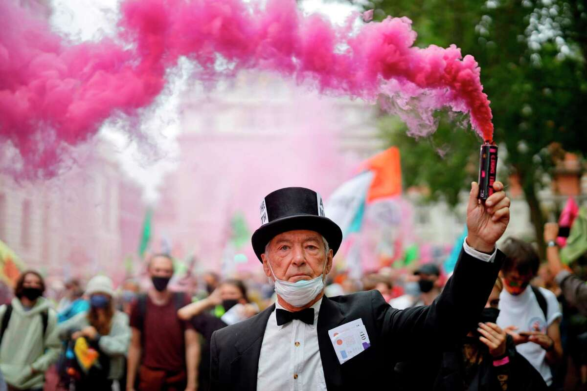 An Extinction Rebellion activist waves a flare during a demonstation in central London on September 3, 2020 on the third day of their new series of 'mass rebellions'. - Climate change protesters converged on the British parliament on September 1, kicking off 10 days of demonstrations to be held across the country by activist group Extinction Rebellion.