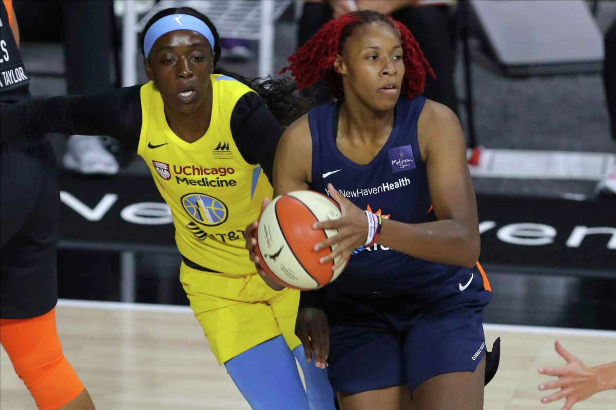Connecticut Sun's Bria Holmes, right, is chased by Chicago Sky's Kahleah Copper during the first half of a WNBA basketball game Saturday, Aug. 8, 2020, in Bradenton, Fla. (AP Photo/Mike Carlson)