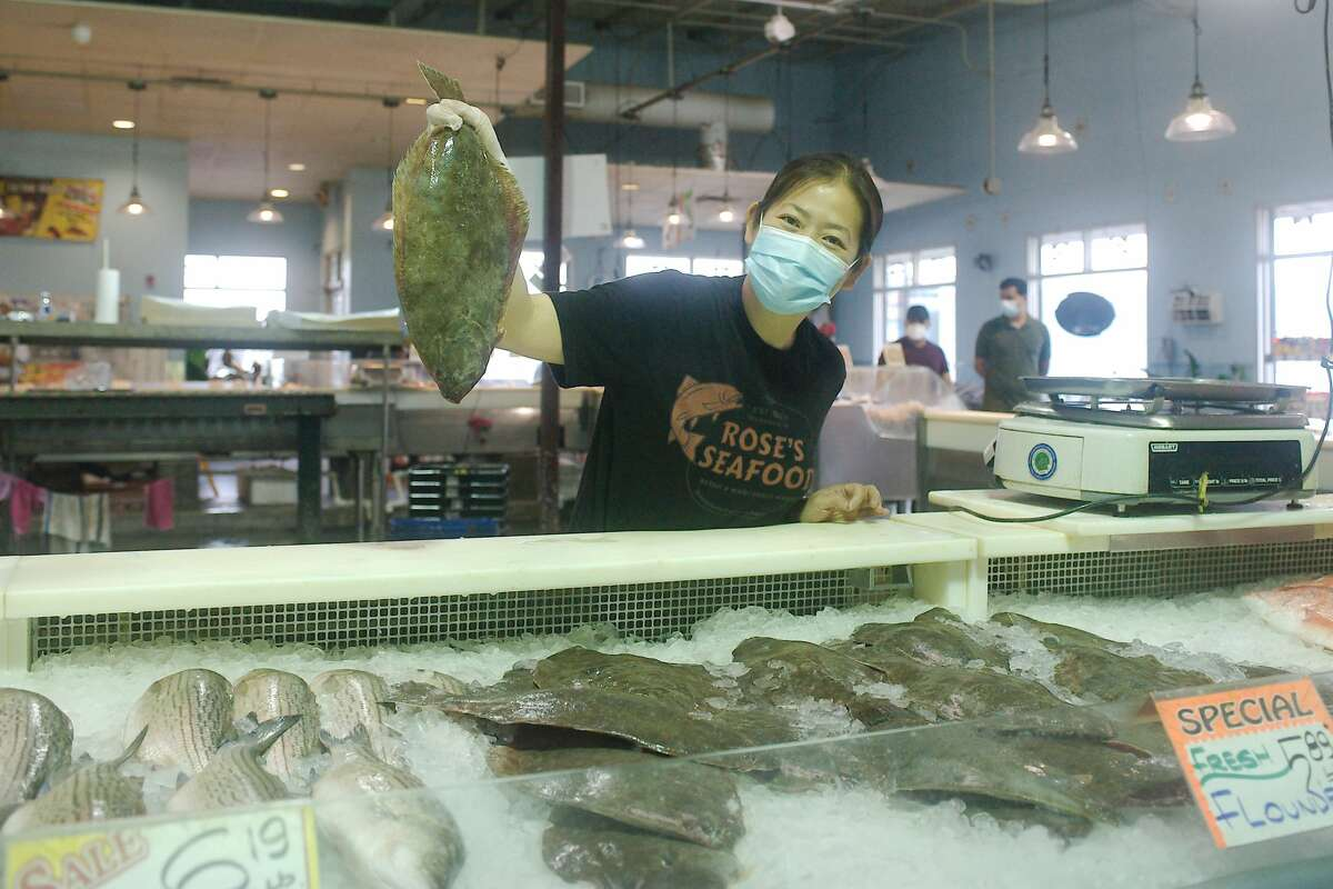 Manager Samantha Tran poses with a fresh caught gulf flounder at Rose's Seafood market in Seabrook. The business at the intersection of Waterfront and Bath has been rebuilt a couple of times after storms.