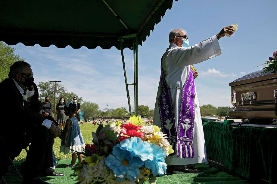 Enrique, left, watches as Deacon Adrian Falcon, from Our Lady of Guadalupe Church, blesses Nora, his wife of almost 44 years, during her burial service at at Sunset Memorial Oaks Cemetery in Del Rio. Nora was hospitalized June 19 with COVID-19. Coronavirus restrictions prevented Enrique and the rest of the family from being at her bedside during her illness. Photo: Lisa Krantz, Staff Photographer / San Antonio Express-News