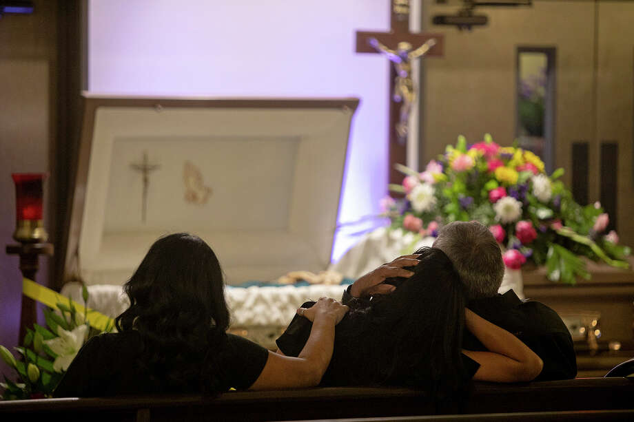 "Vanessa leans her head on her father, Enrique, as her sister, Alex, lays an arm on her shoulder during the July 31 visitation and rosary for their mother and Enrique's wife, Leonor ""Nora"" Rangel, at Trinity Mortuary in Del Rio. Photo: Lisa Krantz, Staff Photographer / San Antonio Express-News"