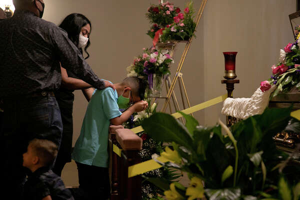 Alex and her husband, Roberto Vasquez Jr., comfort their son, Fabian Vasquez, 8, as he kneels in front of his grandmother's casket during the July 31 visitation at Trinity Mortuary in Del Rio.
