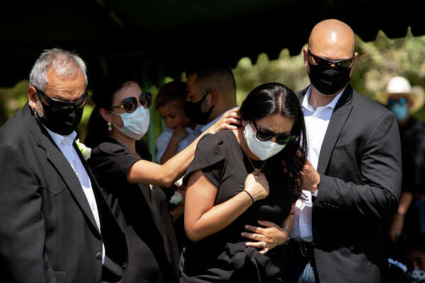 Vanessa, center, grieves for her mother during Nora's burial service. Her father, Enrique, is on the left.