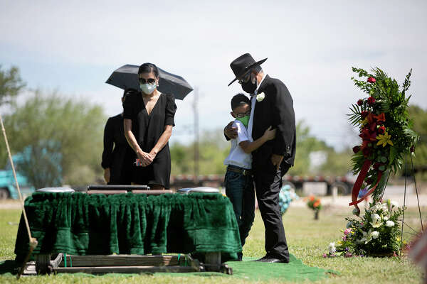 "Fabian Vasquez Jr., 8, embraces his grandfather, Enrique Rangel, after the burial of Fabian's grandmother and Enrique's wife, Leonor ""Nora"" Rangel, at Sunset Memorial Oaks Cemetery in Del Rio on Saturday, August 1, 2020. Family friend Claudia Martin, left, grieves as well."