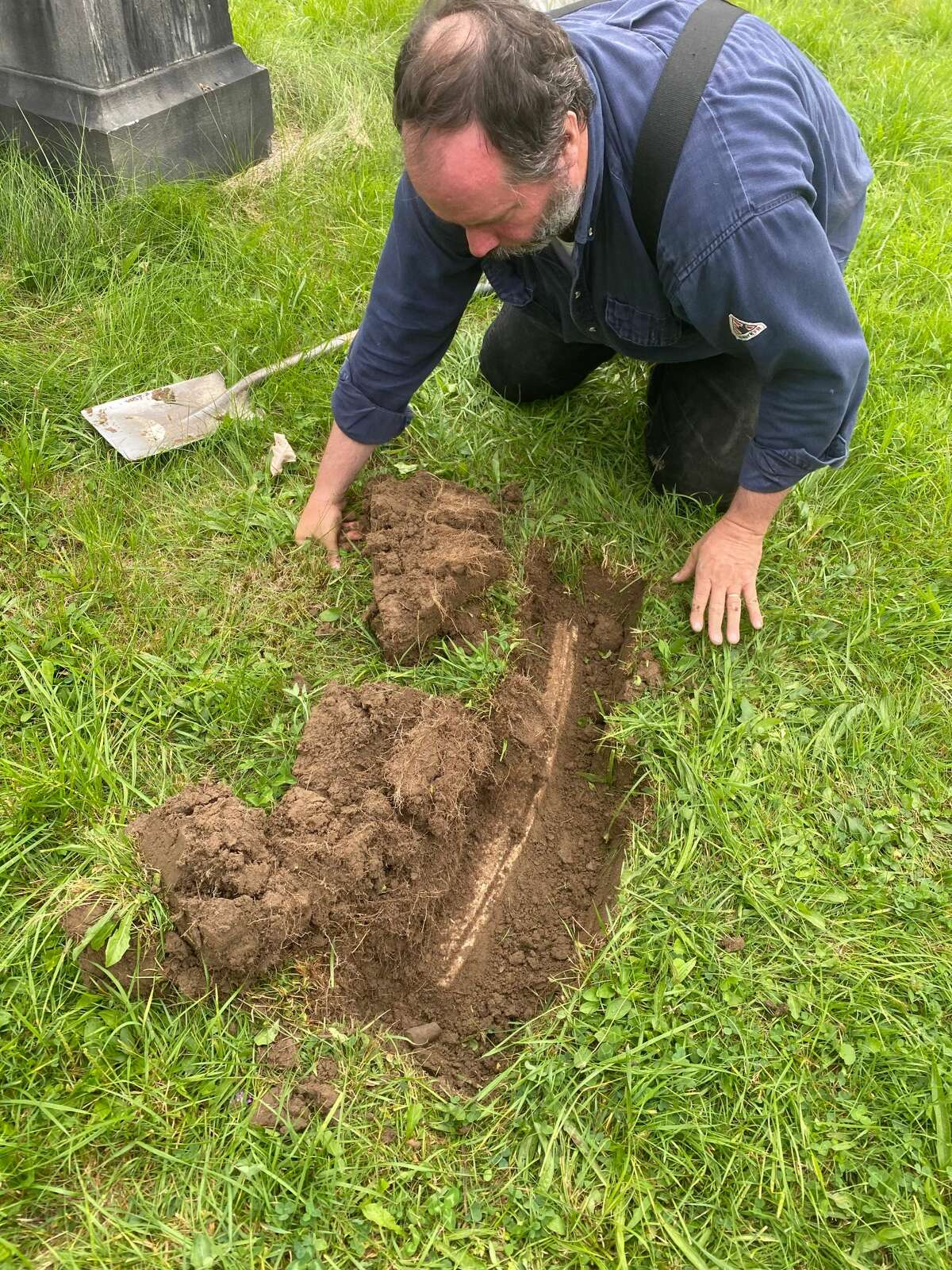 Chris White, owner of Albany Grave Digger, starts to uncover part of the gravestone for the Rev. Nathaniel Paul, who arrived in Albany in 1820 as the founding pastor of what would become First African Baptist Church. White and historian Paula Lemire unearthed the marker earlier this week in Albany Rural Cemetery in Menands. It is presumed to have been buried for a century or more after  being toppled or falling over. (Provided photo.)