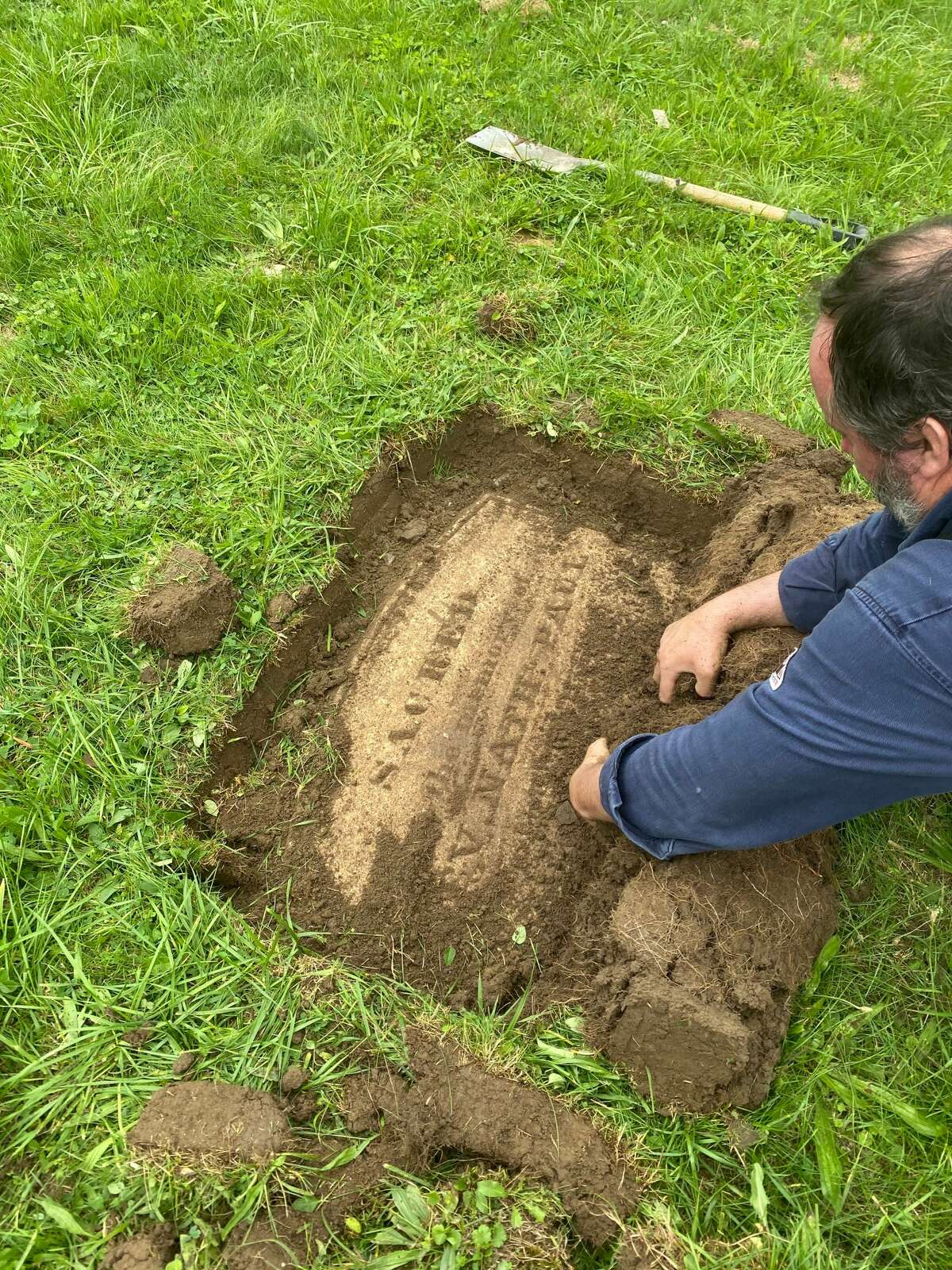 Chris White, owner of Albany Grave Digger, uncovers part of the gravestone for the Rev. Nathaniel Paul, who arrived in Albany in 1820 as the founding pastor of what would become First African Baptist Church. White and historian Paula Lemire unearthed the marker earlier this week in Albany Rural Cemetery in Menands. It is presumed to have been buried for a century or more after  being toppled or falling over. (Provided photo.)