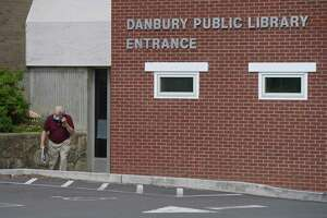 George Raemore, of Danbury, leaves the Danbury Public Library on Thursday afternoon. The library has reopened, with limited services, appointments and curbside pick-up and drop off. Thursday, September 3, 2020, in Danbury, Conn.
